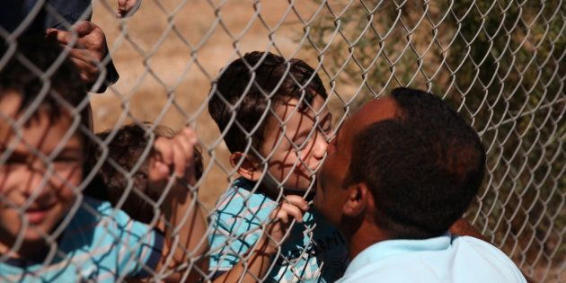Syrian man Ammar Hammasho, who lives in Cyprus, kisses his child who arrived at the refugee camp in Kokkinotrimithia...