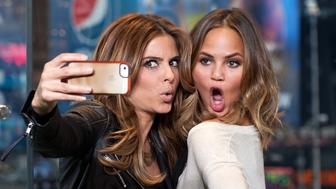 "NEW YORK, NY - JANUARY 31:  (L-R) Maria Menounos (L) and Chrissie Teigen visit ""Extra"" in Times Square on January 31, 2014 in New York City.  (Photo by D Dipasupil/Getty Images for Extra)"