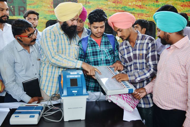 Indian electoral officials demonstrate how to use an Electronic Voting Machine (EVM) and Voter-Verified Paper Audit Trail (VVPAT) to passengers during a voter awareness programme.