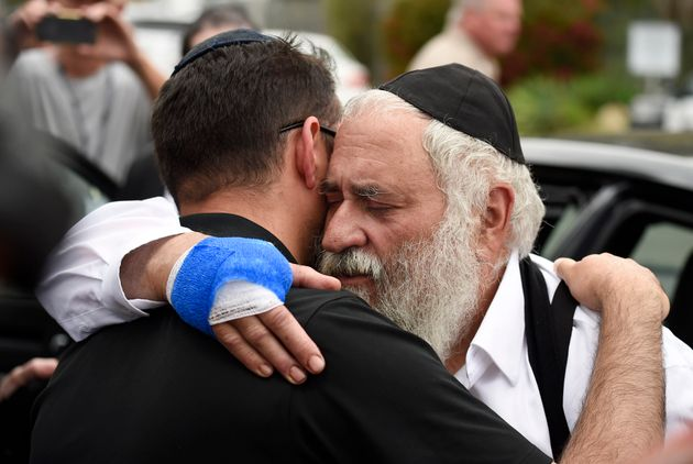 Rabbi Yisroel Goldstein (right) is hugged as he leaves a news conference at the Chabad of Poway synagogue...