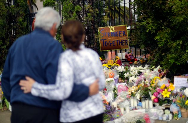 A couple embrace near a growing memorial across the street from the Chabad of Poway synagogue in Poway,...