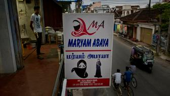 A billboard displays garments worn by Muslim women, at a women's clothing shop in Kattankudy, Sri Lanka, Monday, April 29, 2019. After being targeted by Islamic State suicide bombings on Easter, Sri Lanka has banned the niqab face veil, which increasingly has been seen in Muslim areas of the island nation's east. (AP Photo/Gemunu Amarasinghe)