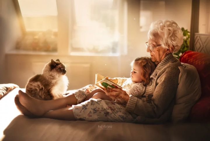 A grandma and her toddler granddaughter read in a comfy spot.