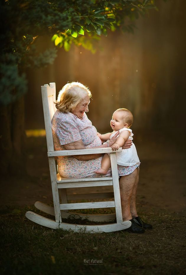 A great-grandma and her great-granddaughter sit in a rocking