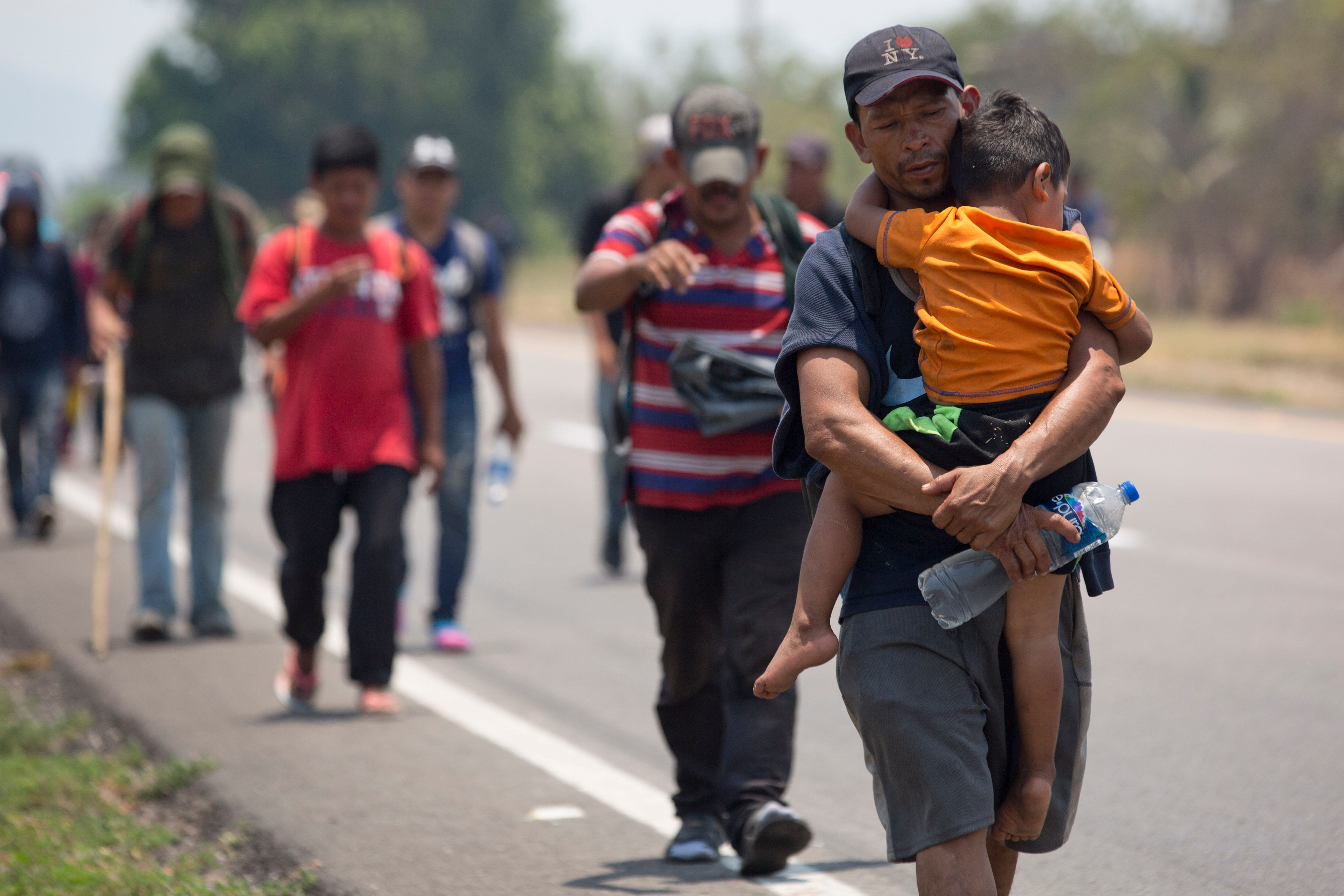 A Central American migrant man carrying a child walks along the highway through Tonala, Chiapas state, Mexico, Sunday, April 21, 2019, as a migrant caravan heads to the U.S. border. The outpouring of aid that once greeted Central American migrants as they trekked in caravans through southern Mexico has been drying up, so this group is hungrier, advancing slowly or not at all, and hounded by unhelpful local officials. (AP Photo/Moises Castillo)