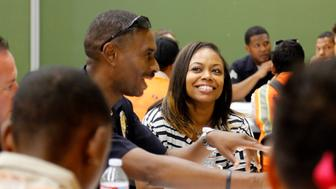 Rodney King's daughter Lora King, 32, and Los Angeles Police Officer Rashad Sharif, left, talk with a group of young people who have had their own run-ins with police at a meeting of the Los Angeles Conservation Corps, which provides at-risk youth with job training, education and work, in downtown Los Angeles Thursday, Sept. 15, 2016. She was just 7 when her father was beaten by the Los Angeles Police Department. Her message: It's more important to build bridges with officers than to stand against the, and that a whole police department can't be judged by the actions of a few.(AP Photo/Reed Saxon)