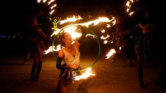 """Burning Man participants from the """"Revolutionary Motion"""" fire conclave out of Washington, D.C. spin fire hoops in front of the effigy of """"The Man"""" just before the effigy is burned at the culmination of the annual Burning Man arts and music festival in the Black Rock desert of Nevada, U.S. September 2, 2017. REUTERS/Jim Bourg   FOR USE WITH BURNING MAN RELATED REPORTING ONLY. FOR EDITORIAL USE ONLY. NOT FOR SALE FOR MARKETING OR ADVERTISING CAMPAIGNS. NO THIRD PARTY SALES. NOT FOR USE BY REUTERS THIRD PARTY DISTRIBUTORS"""