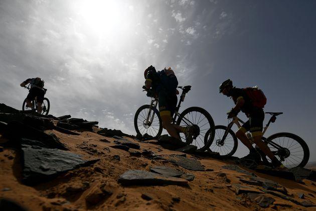 Des cyclistes poussent leur vélo dans le dunes de sable lors de la 2e étape de la compétition...