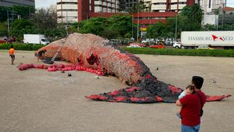 A father cuddles his baby as he watches workers put finishing touches on an art installation of a beached blue whale with its intestines full of plastics to depict the plastics pollution of the world's oceans Friday, April 26, 2019, outside the Cultural Center of the Philippines in Manila, Philippines. The giant blue whale art, that will be on display until May 26, 2019, was the brainchild of Filipino artist Biboy Royong and executed by fellow artist Roderick Banares. (AP Photo/Bullit Marquez)