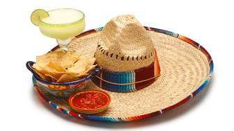 A margarita, salsa and chips sitting on a sombrero.