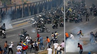 Opponents to Venezuela's President Nicolas Maduro confront loyalist Bolivarian National Guard troops firing tear gas at them, outside La Carlota military airbase in Caracas, Venezuela, Tuesday, April 30, 2019. Venezuelan opposition leader Juan Guaidó took to the streets with activist Leopoldo Lopez and a small contingent of heavily armed troops early Tuesday in a bold and risky call for the military to rise up and oust socialist leader Nicolas Maduro. (AP Photo/Fernando Llano)