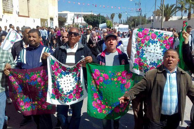 Des proches des victimes portant les foulards portées par les ouvrières agricoles