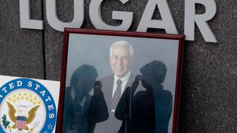 Women are reflected in the glass of photograph Sen. Richard Lugar places at the entrance to the Richard G. Lugar Plaza outside the City-County Building in Indianapolis, Monday, April 29, 2019. Lugar, 87, died Sunday. (AP Photo/Michael Conroy)
