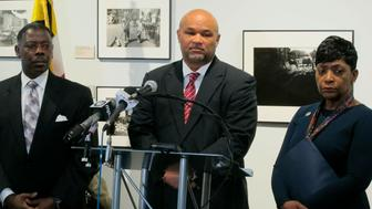 Deleget Dereck Davis, center, takes questions from reporters after Del. Adrienne Jones, right, announced she would withdraw from the race for speaker of the Maryland House of Delegates and support Davis on Friday, April 26, 2019 in Baltimore. Del. Talmadge Branch is standing left. (AP Photo/Brian Witte)