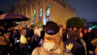 A group gathers outside the Tree of Life Synagogue for a vigil to honor the victims of the Saturday attack on a synagogue in California Saturday April 27, 2019 in the Squirrel Hill neighborhood of Pittsburgh. It is six months to the day that a gunman shot and killed 11 people while they worshipped at the Tree of Life Synagogue on Oct. 27, 2018. (AP Photo/Gene J. Puskar)
