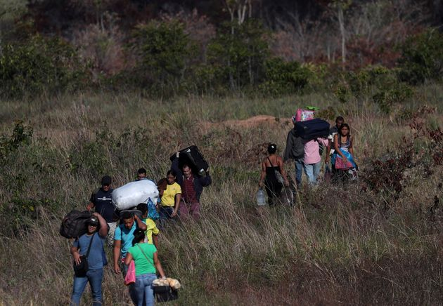 People cross through a field at the Brazil-Venezuela border in Pacaraima, Brazil, in February. More than...