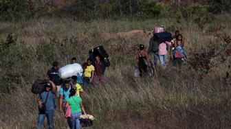 People cross through a field at the border between Brazil and Venezuela in Pacaraima, Brazil February 28, 2019. REUTERS/Ricardo Moraes