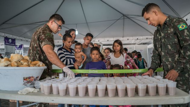 Venezuelan families wait for food and drink inside a refugee reception center in Pacaraima, Brazil, in...