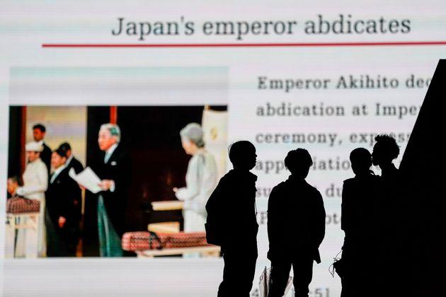 天皇陛下の退位の儀式の様子を街中のスクリーンで見る人々 イメージ画像