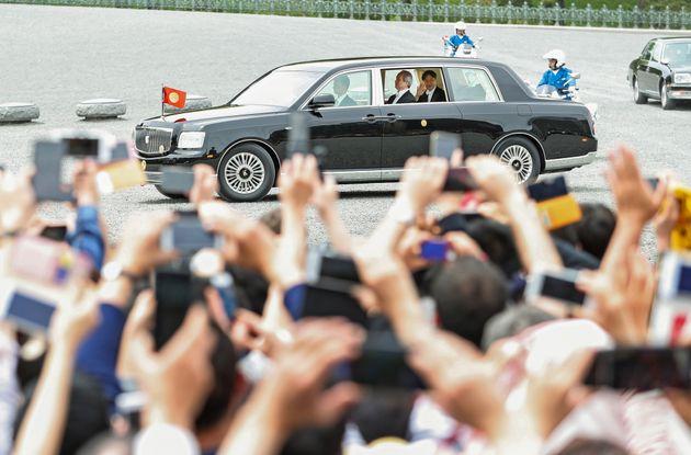 集まった人たちに手を振って皇居を出られる新天皇陛下=1日午後、東京都千代田区