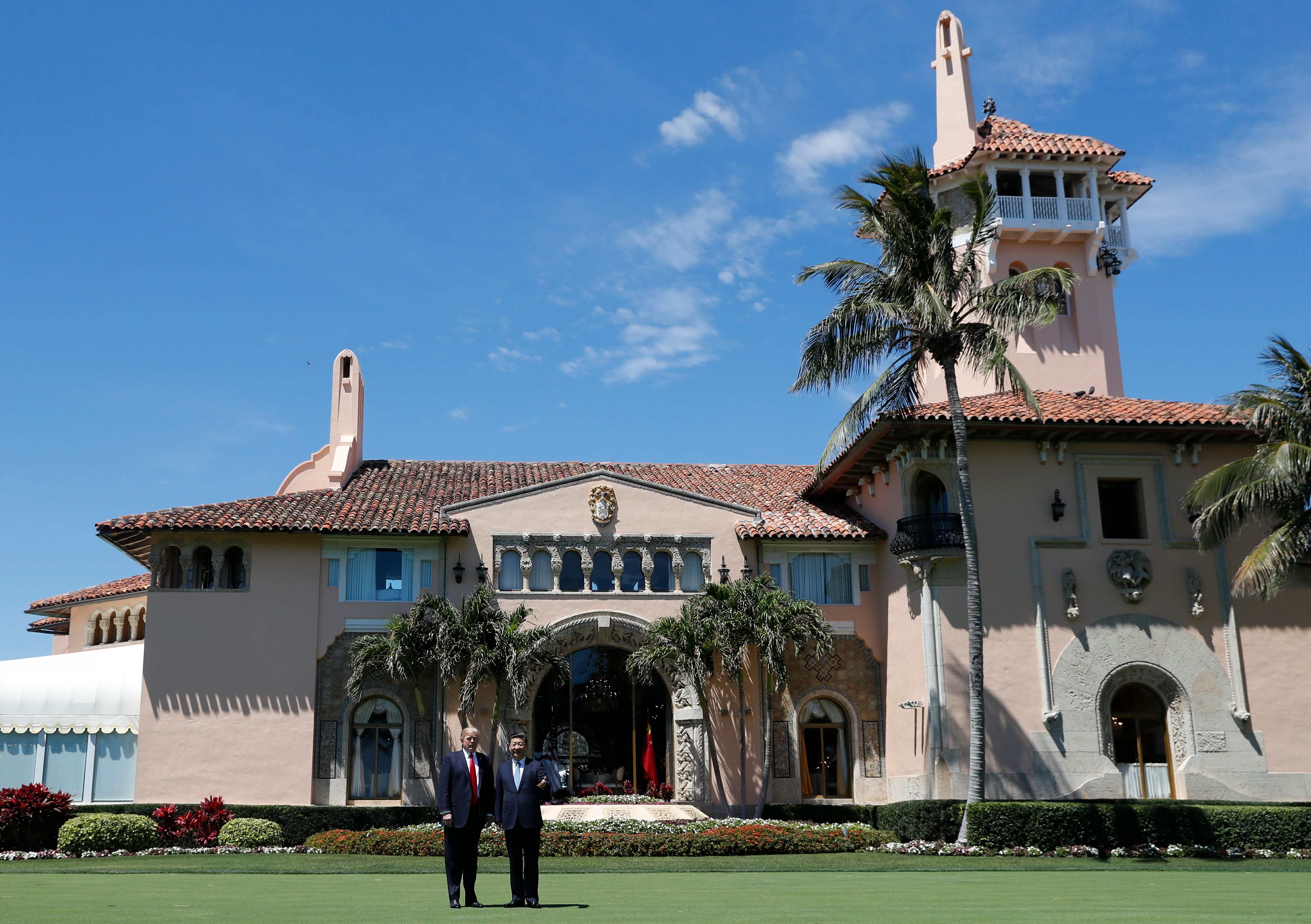 President Donald Trump and Chinese President Xi Jinping pause for photographs as they walk together at Mar-a-Lago, Friday, April 7, 2017, in Palm Beach, Fla. Trump was meeting again with his Chinese counterpart Friday, with U.S. missile strikes on Syria adding weight to his threat to act unilaterally against the nuclear weapons program of China's ally, North Korea. (AP Photo/Alex Brandon)