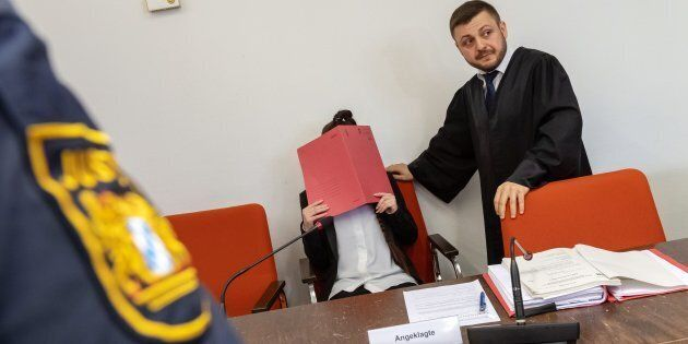 Defendant Jennifer W (C) hides her face behind a folder and sits next to her lawyer Ali Aydin (R) as...