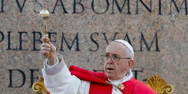Pope Francis asperses holy water as he celebrates Palm Sunday Mass in St. Peter's Square at the Vatican,...