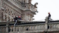 Alpinisti al lavoro per coprire Notre Dame con un telone anti