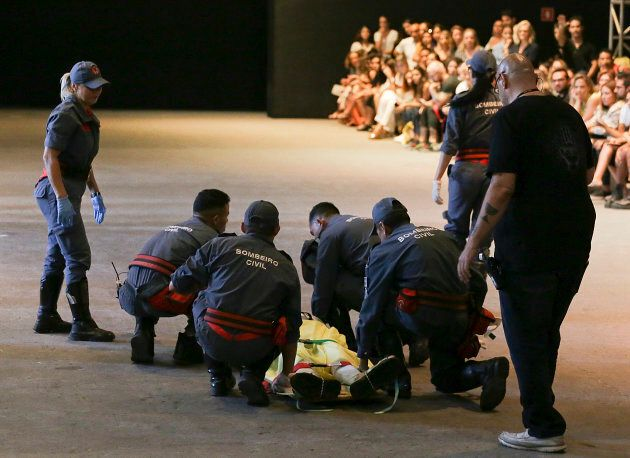 Model Tales Soares is taken from the catwalk by paramedics after he collapsed during Sao Paulo Fashion...