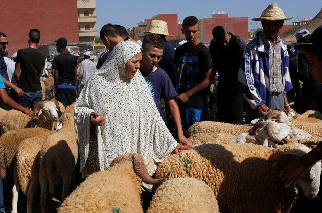 Une femme achète un mouton sur un marché au bétail, avant l'Aïd al-Adha, dans...