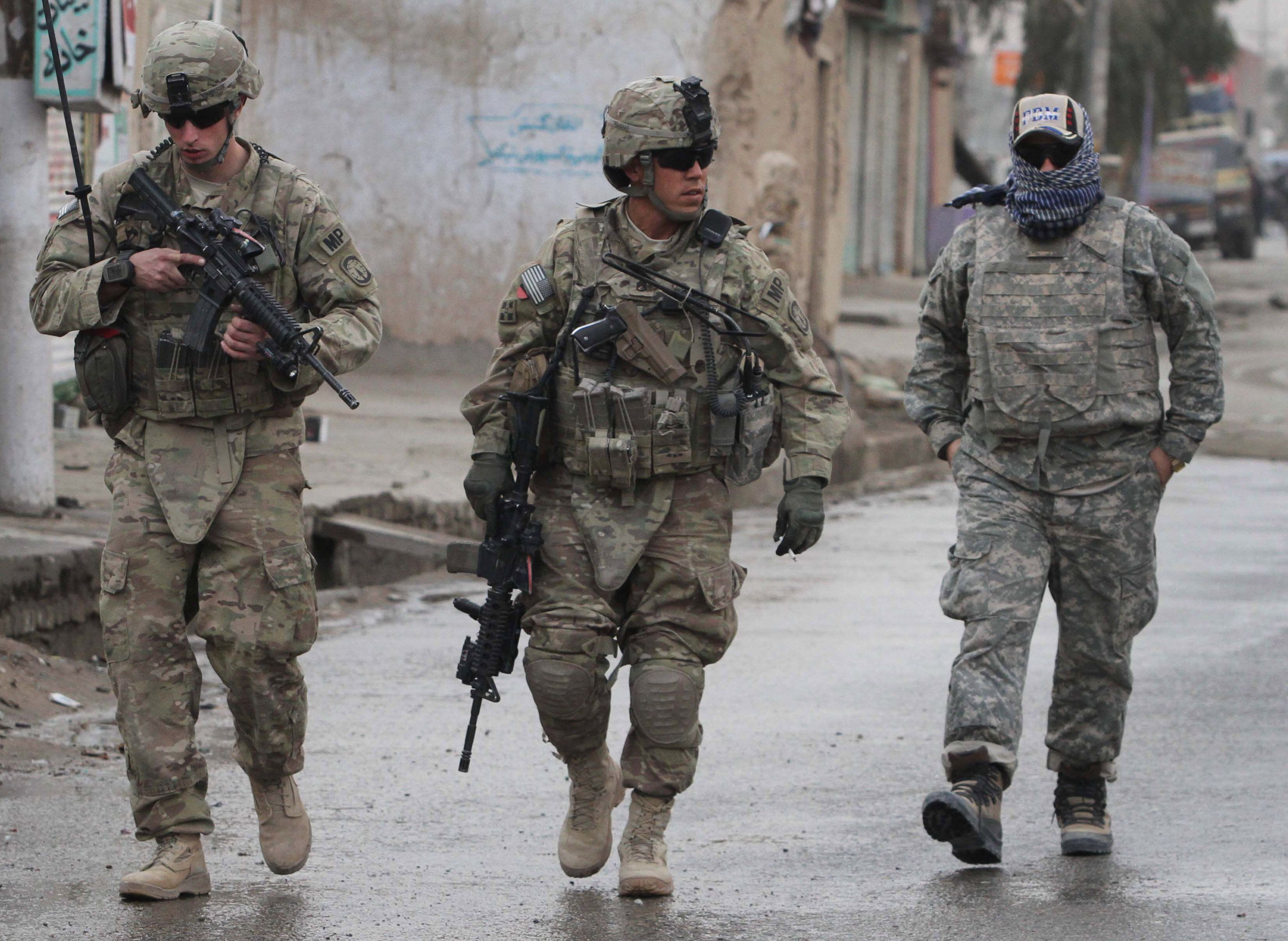 U.S. soldiers walk with their Afghan translator near the scene of a suicide attack in Kandahar, south of Kabul, Afghanistan, Tuesday, Jan. 3, 2012. A suicide bomber driving a motorcycle killed four civilians and a police officer in southern Afghanistan's Kandahar city on Tuesday, police said.  (AP Photo/Allauddin Khan)