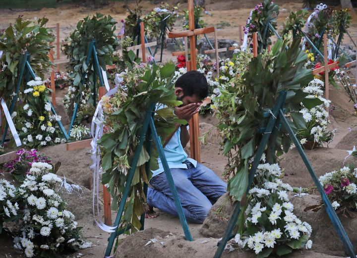 A Sri Lankan relative of a victim of Easter Sunday bomb blasts pays tribute at the burial site.