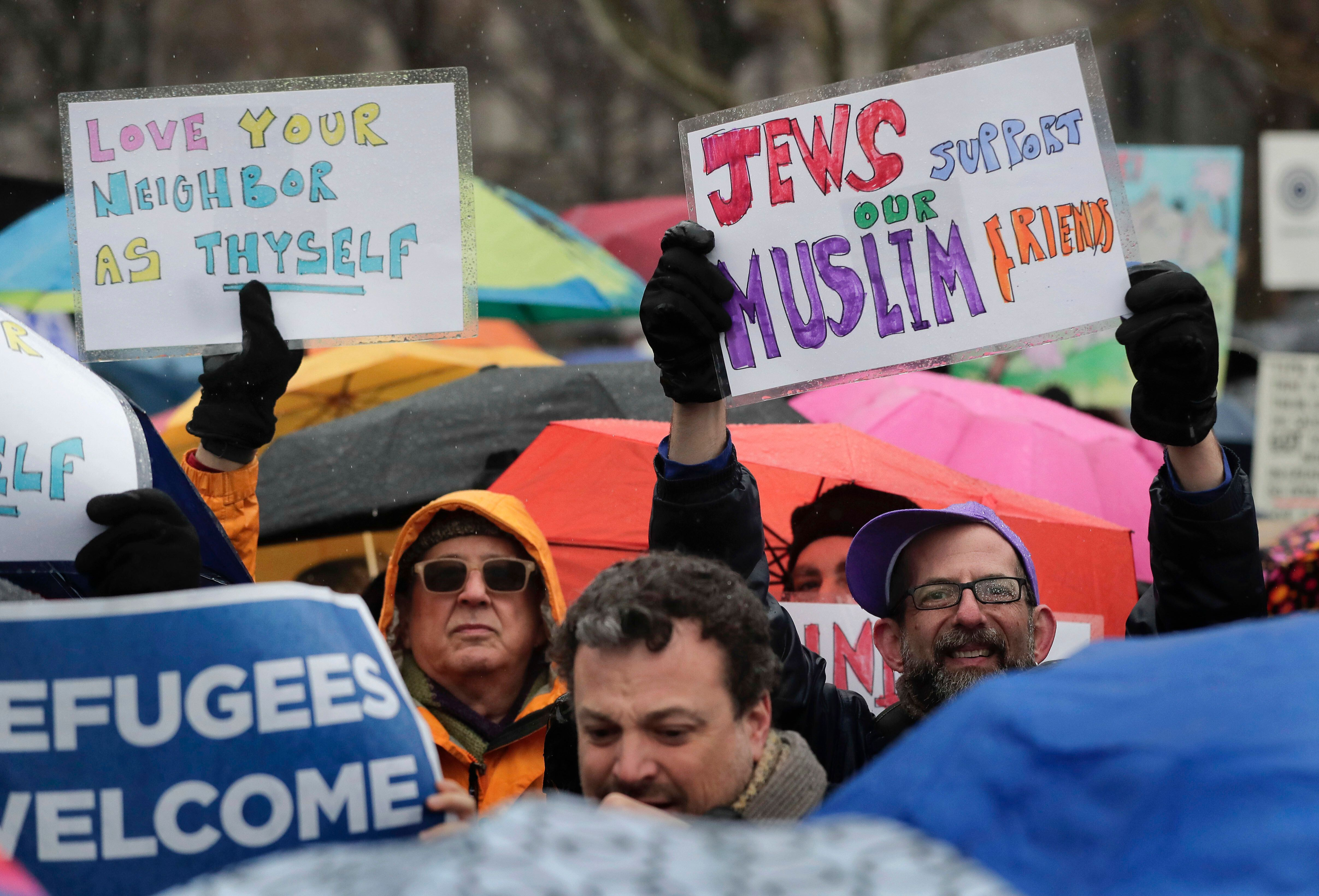 Demonstrators hold up signs during a rally in Battery Park organized by the Hebrew Immigrant Aid Society to mark a National D