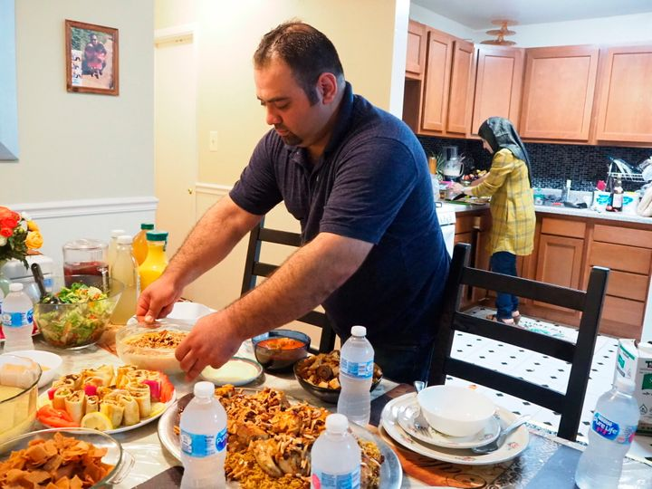 In this May 25, 2018, photo, Syrian refugee Majed Abdalraheem, 29, sets the table at his home in Riverdale, Md., as he and hi