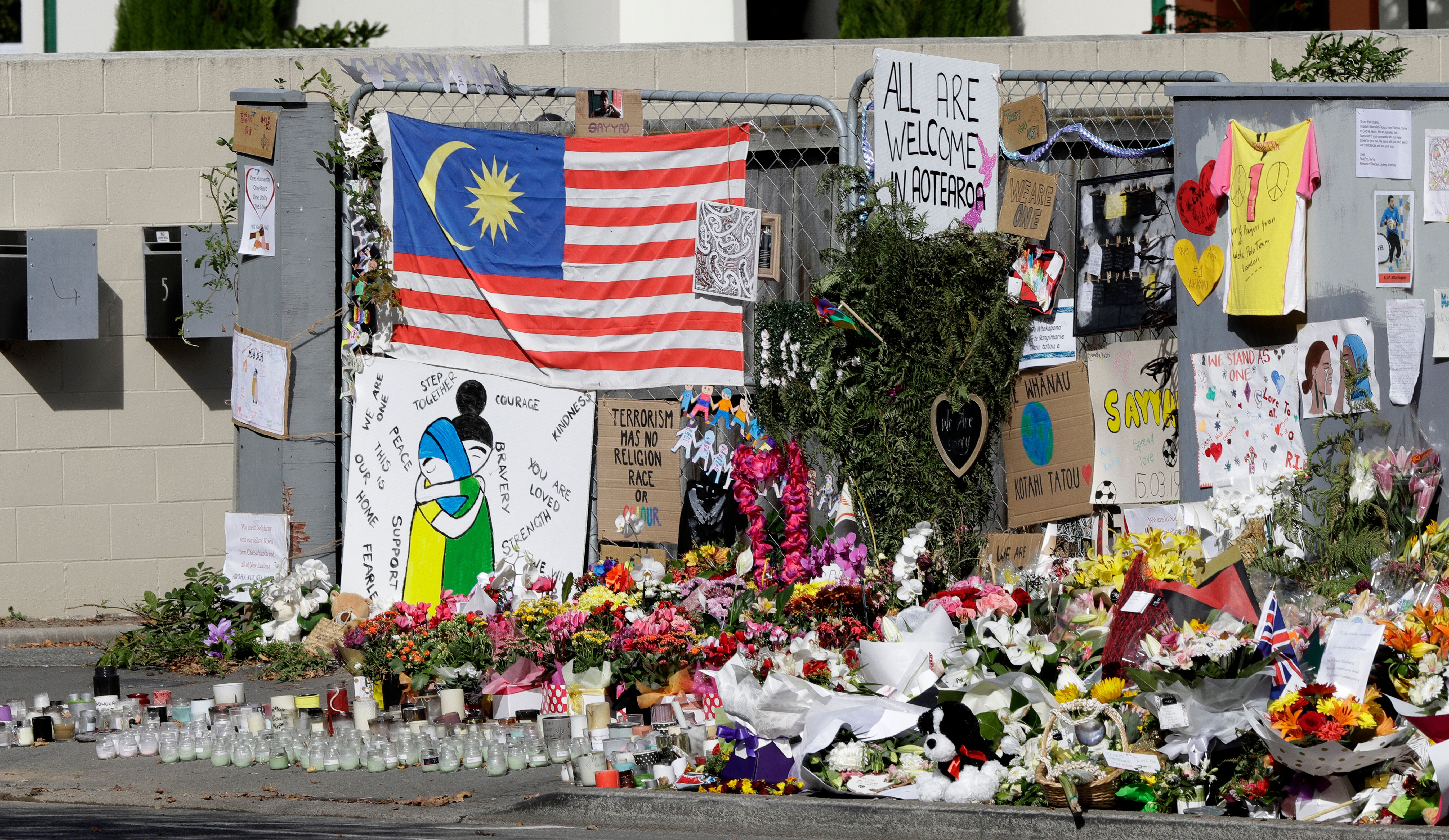 Tributes hang on the fence outside the Al Noor mosque in Christchurch, New Zealand, Friday, March 22, 2019. In a day without precedent in New Zealand, people across the country were planning to observe the Muslim call to prayer as the nation reflected on the moment one week ago when 50 people were slaughtered at two mosques. (AP Photo/Mark Baker)