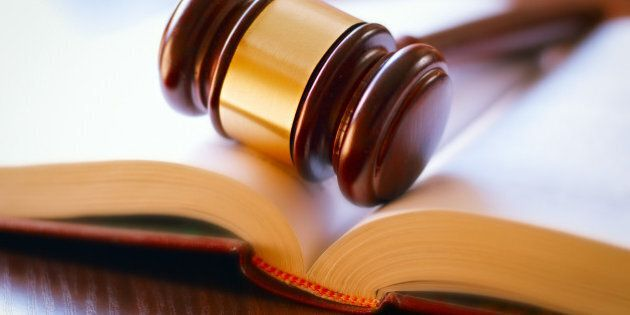 brown gavel and open book on a wooden table of the law in the