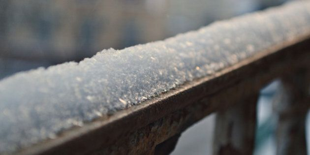 A snow cap on a metal railing of a