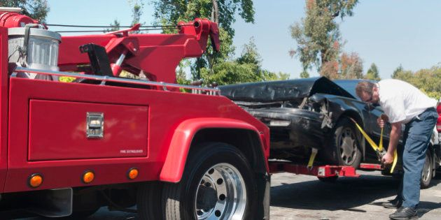 Tow truck driver securely strapping a wrecked car in preparation for towing