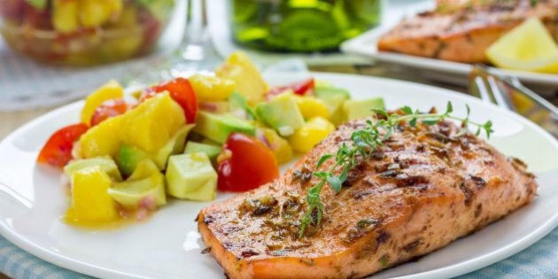 Spice grilled salmon with mango-avocado salsa on a white