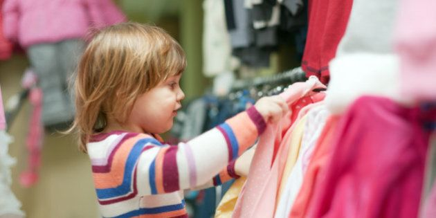 2 years baby girl chooses clothes at fashionable