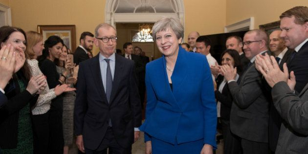 Britain's Prime Minister Theresa May and her husband Philip are welcomed by staff inside 10 Downing Street,...