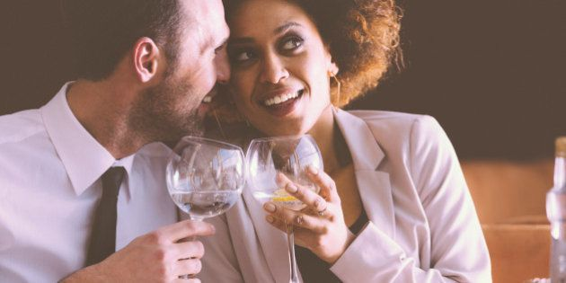 Happy couple - afro american woman and caucasian man in elegant outfits having lunch or dinner in restaurant,...