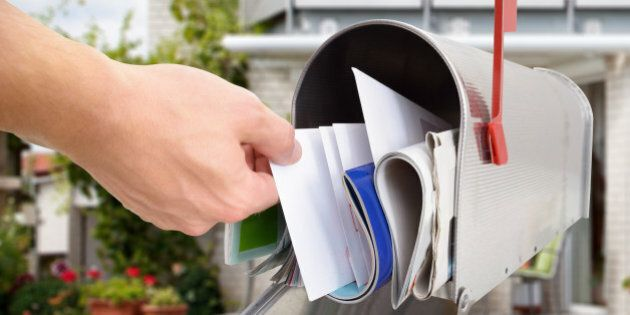 Close-up Of Man's Hand Taking Letter From Mailbox Outside