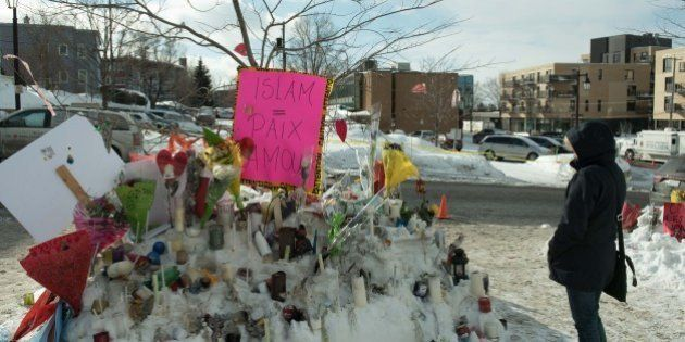 People place messages and flowers near a mosque that was the location of a shooting spree in Quebec City,...