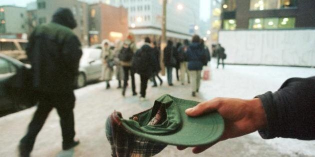 MONTREAL, CANADA: A homeless man begs in downtown Montreal 20 January, 2000 as the temperature remained...