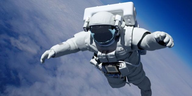 Astronaut in space above the clouds of the