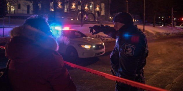 A Canadian police officer talks to a woman after a shooting in a mosque at the Québec City Islamic cultural...