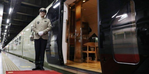 This picture taken on April 26, 2017 shows a crew member standing next to the Train Suite Shiki-Shima, operated by East Japan Railway, at Ueno Station in Tokyo during a press preview.The luxury sleeper Shiki-Shima, which can accommodate up to 34 passengers, has 10 cars, including a lounge car, a dining car and two observatory cars. The train has only 17 cabins, all suites, and the most expensive room, known as Shiki-Shima Suite, is priced at 950,000 yen (8480 USD) per person when shared by two people.  / AFP PHOTO / JIJI PRESS / str / Japan OUT        (Photo credit should read STR/AFP/Getty Images)