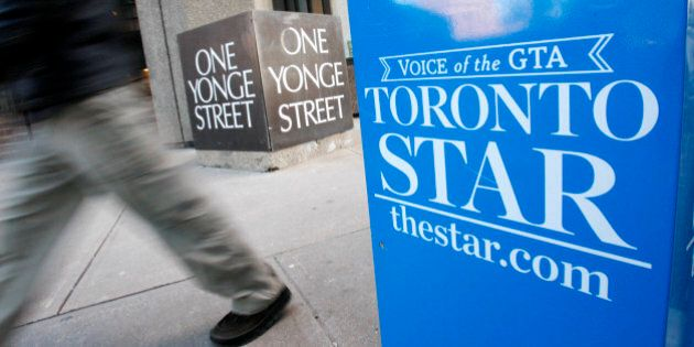A pedestrian walks past a Toronto Star newspaper box in front of the Toronto Star building at One Yonge...