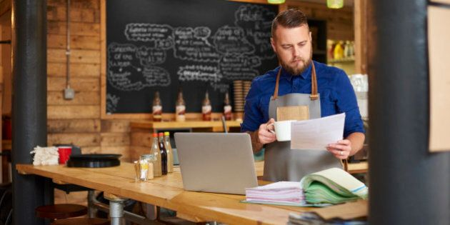 a coffee shop owner checks the delivery notes in his bookkeeping folder on the counter of his busy coffee...